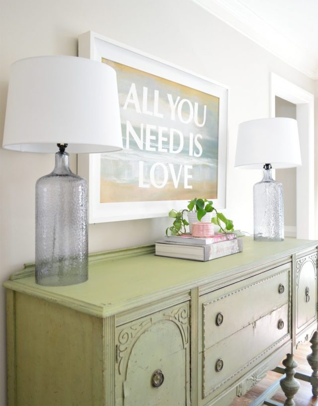 Dining room with vintage green buffet and green ivy plant under All You Need Is Love painting