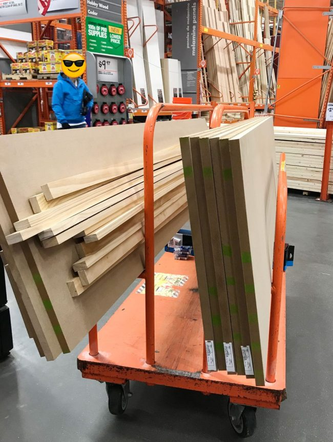cart full of MDF and wood pieces for pantry shelf project