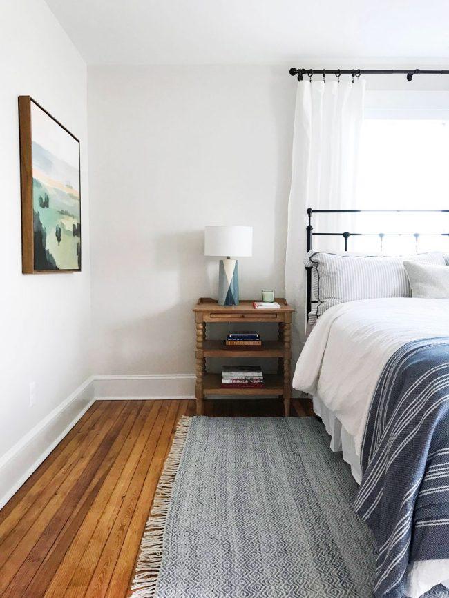 metal headboard in beachy blue bedroom with pine floors
