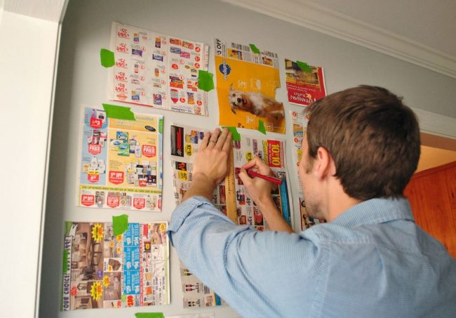 John marking placement of gallery wall using paper templates