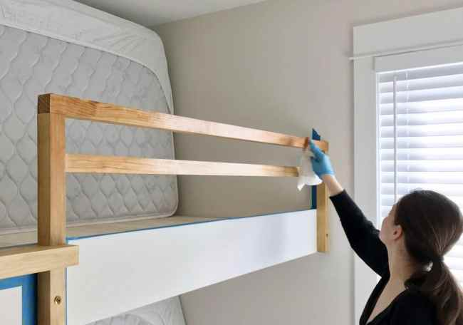 Sherry applying stain to bunk bed railing for raw wood look
