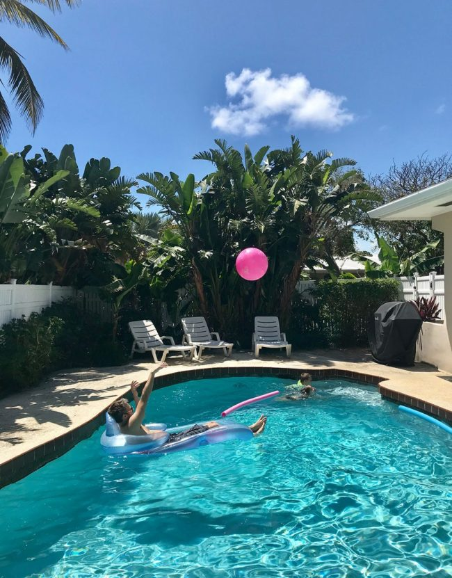 playing in the pool with palm trees around it at beach rental on terra mar island