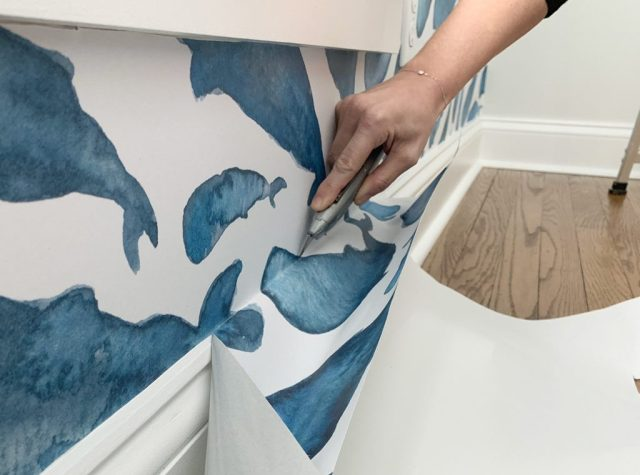 Cutting Off Excess Removable Wallpaper Along Baseboard