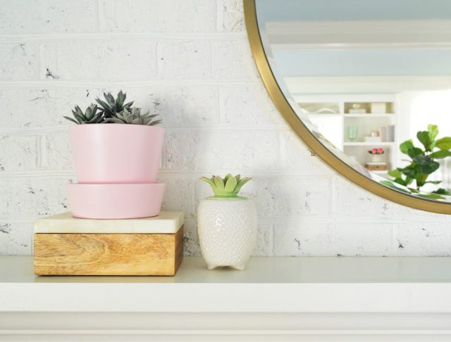Faux succulents on living room fireplace mantle next to round gold mirror