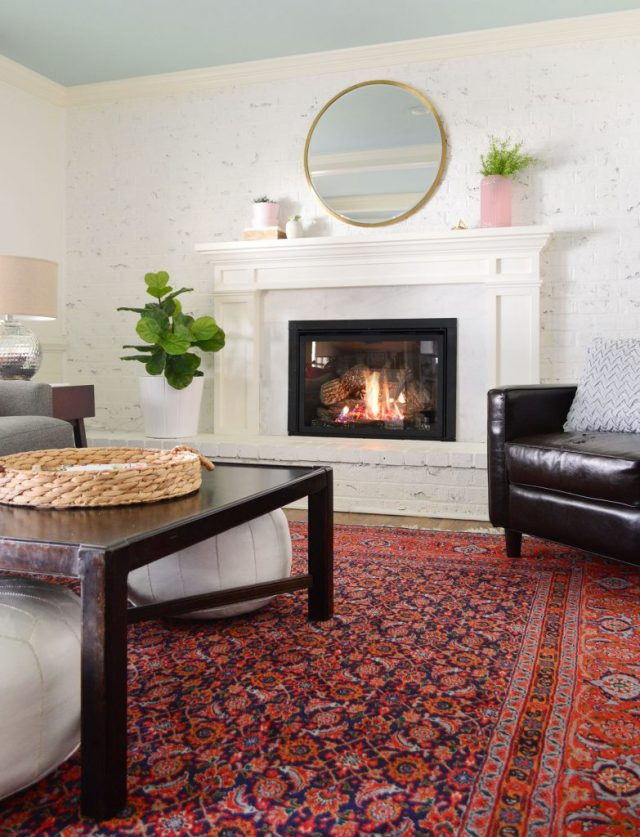 Faux greenery in living room with white walls and red vintage rug