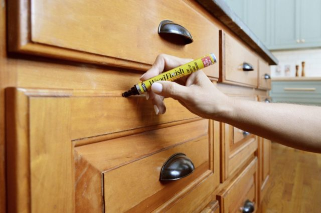 Sherry Applying Stain Marker To Wood Cabinets