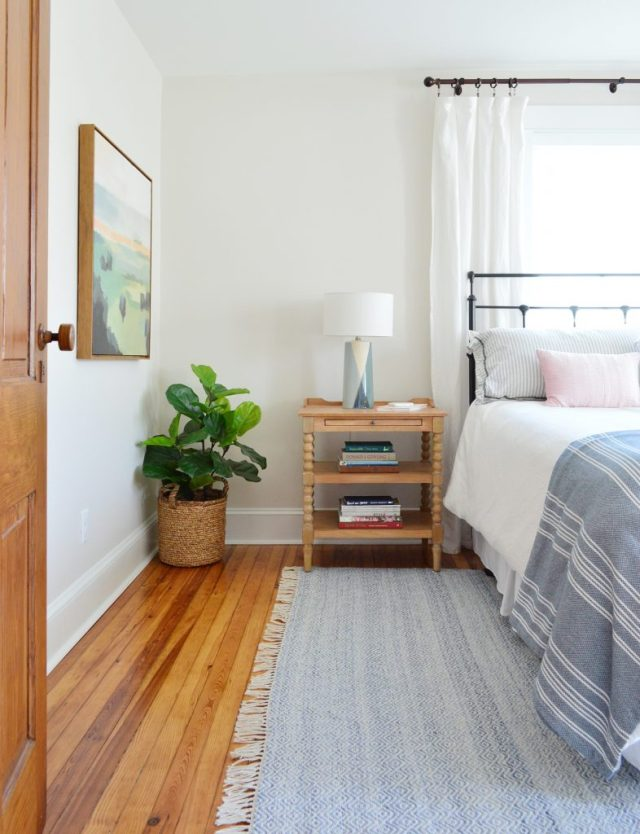 Beach House Front Bedroom With Blue Rug And Wooden Nightstand
