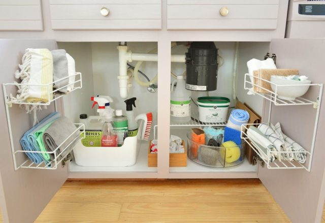 Under sink cleaning supply storage in kitchen with mauve cabinets