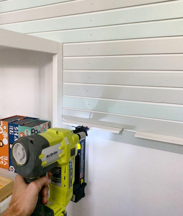 Nail Gun Attaching Smaller Lattice Pieces Onto Wall Next To Bookshelf