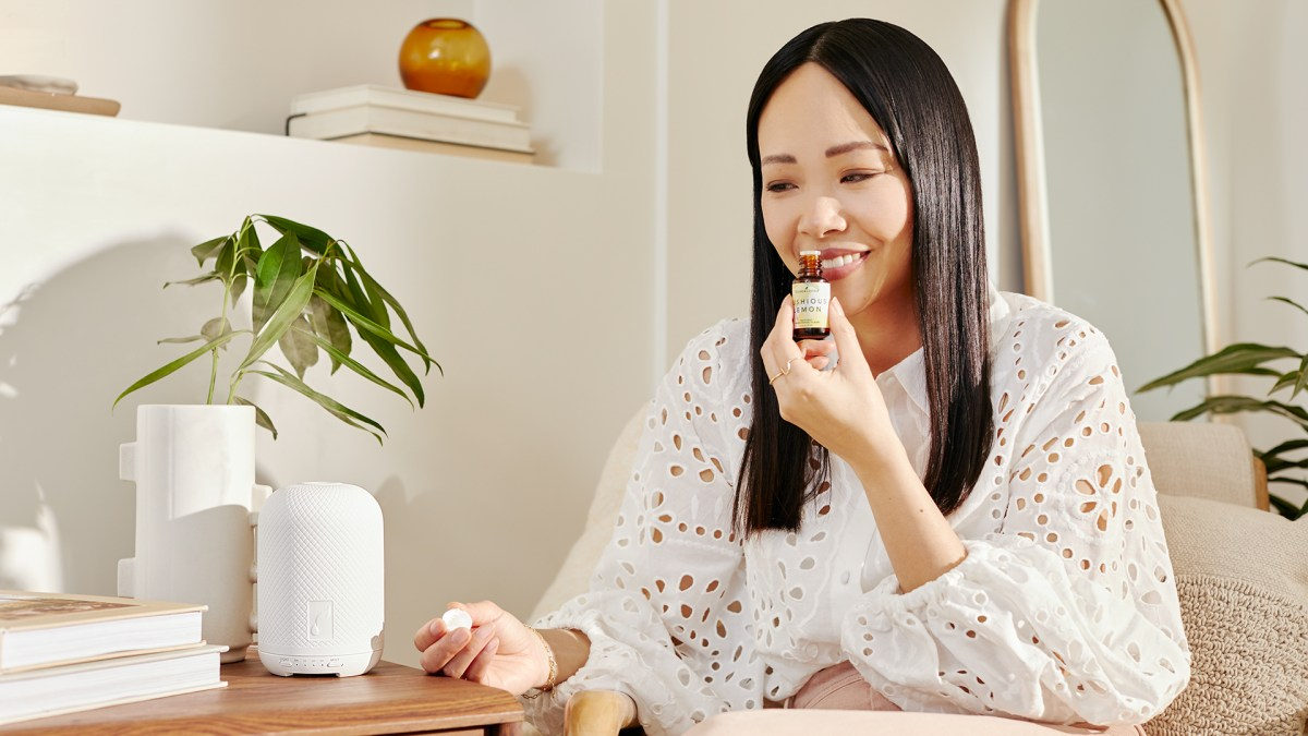 Woman smelling Lushious Lemon Essential Oil and smiling - Young Living Lavender Life blog