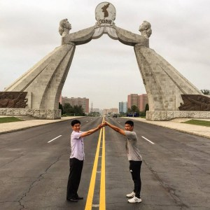 Two men imitate the pose of the Arch of Reunification on the Thongil Highway, just outside Pyongyang.  -- Korean unification