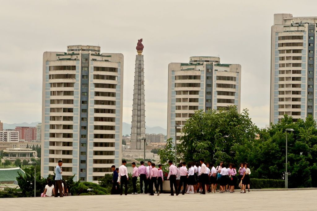 A group of North Korean students walks by the Juche Tower in Pyongyang