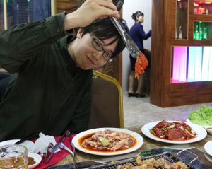 A tourist with Korean BBQ at a Pyongyang restaurant.