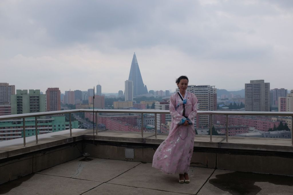 A local guide on top of the Arch of Triumph in Pyongyang with the Ryugyong hotel standing behind her