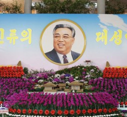A large picture of Kim Il Sung surrounded by kimilsungia and kimjongilia flowers.