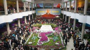 North Koreans gather at a floral arrangement in honour of Kim Il Sung on the Day of the Sun.