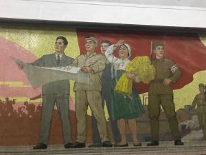 A group of factory workers and a woman carrying a bushel of wheat on a Pyongyang Metro Mural.