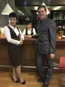 Making a North Korea documentary: Justin, in his North Korean suit, hobnobs with a Korean waitress
