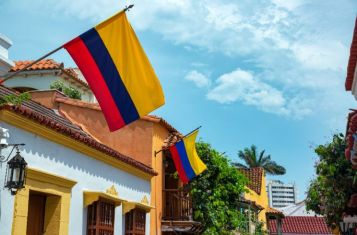 Low Angle View Of Colombian Flags On Houses In City