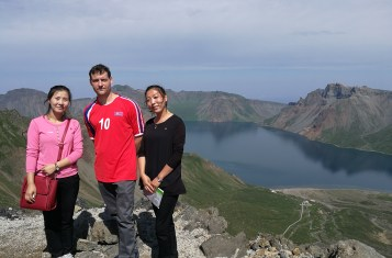 Samjiyon County -- two Koreans and a foreign man stand in front of the crater lake at Mount Paekdu.