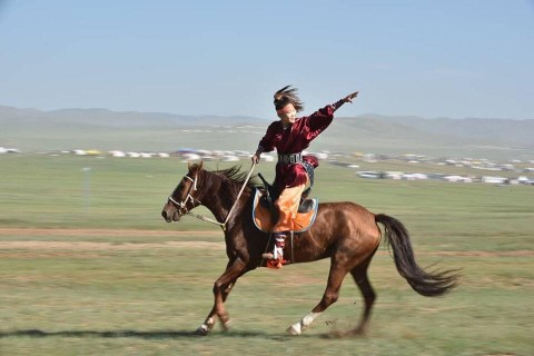 A rider strikes a pose whilst galloping in the run-up to a Mongol horse race.