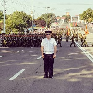Festivals in Transnistria: a police officer stands guard as soldiers march behind him in Tiraspol, Transnistria.