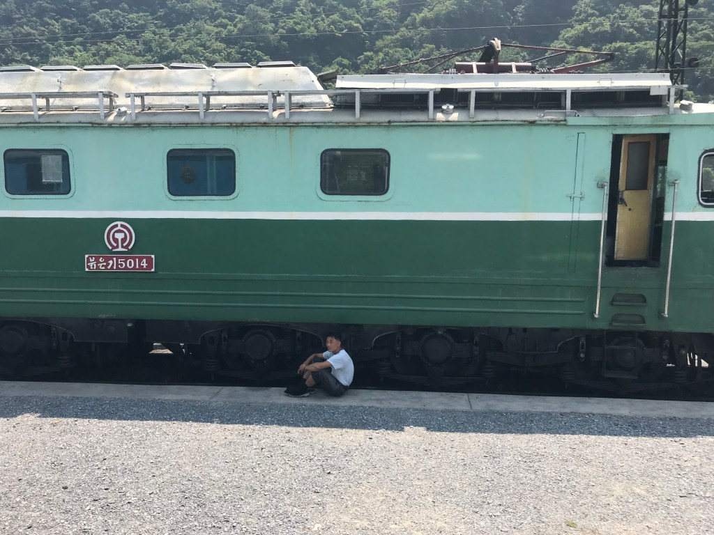 Moscow to Pyongyang: a North Korean boy hides from the sun in the shade of a domestic train carriage.