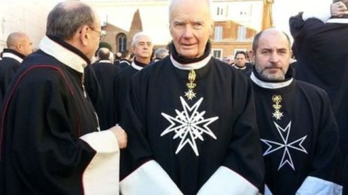 Three men dressed in the black robes of the Sovereign Military Order of Malta stand in the street.