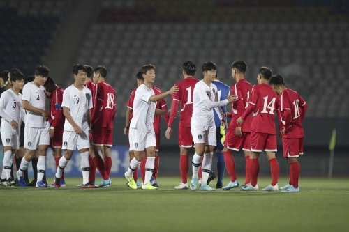 The national squads of North and South Korea greet other before playing their qualifier in an empty Pyongyang stadium.