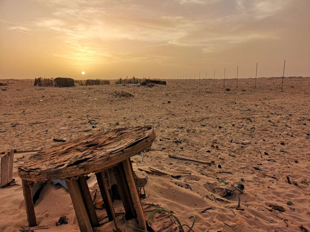 Overland tours: a stunning shot of the Saharan Desert at sunset, with an old wooden spindle in the foreground.