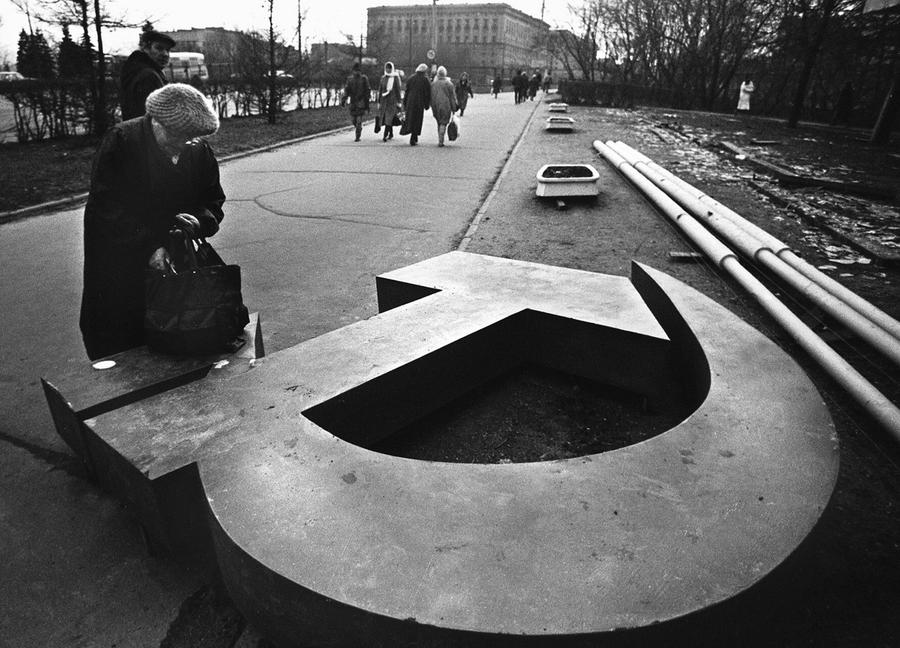 A woman looks at a downed hammer and sickle in a post-USSR country.