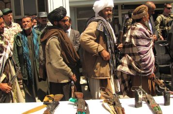 Taliban fighters return their weapons