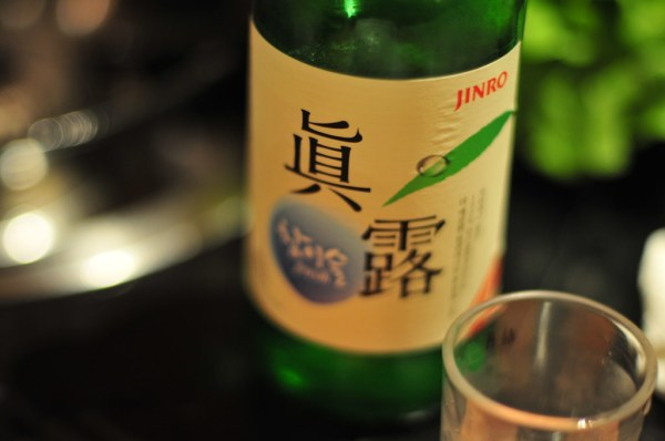 A glass of soju is being prepared next to a soju bottle