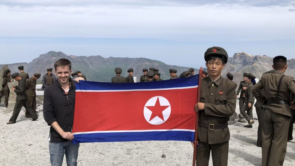 Simon holding the flag of the DPRK on Mt Paektu during his Pyongyang Korean Language Study Tour