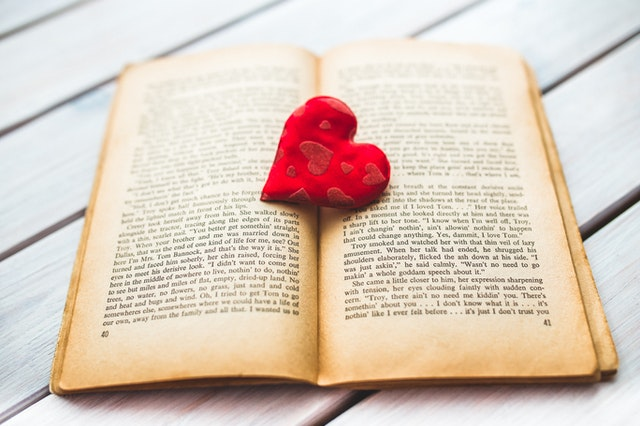 Red felt heart on old book