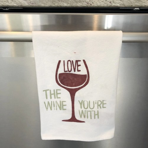 Towel with the word love inside a wine glass surrounded by the phrase hte wine you're with