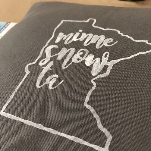 Pillow with an outline of the state of Minnesota and the phrase minnie snow ta inside