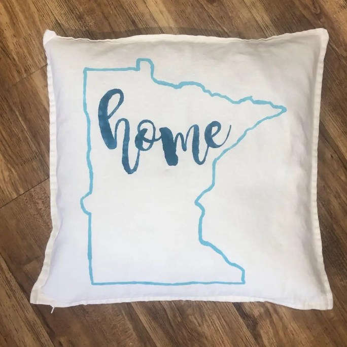 Pillow with the outline of the state of Minnesota and home in the center.