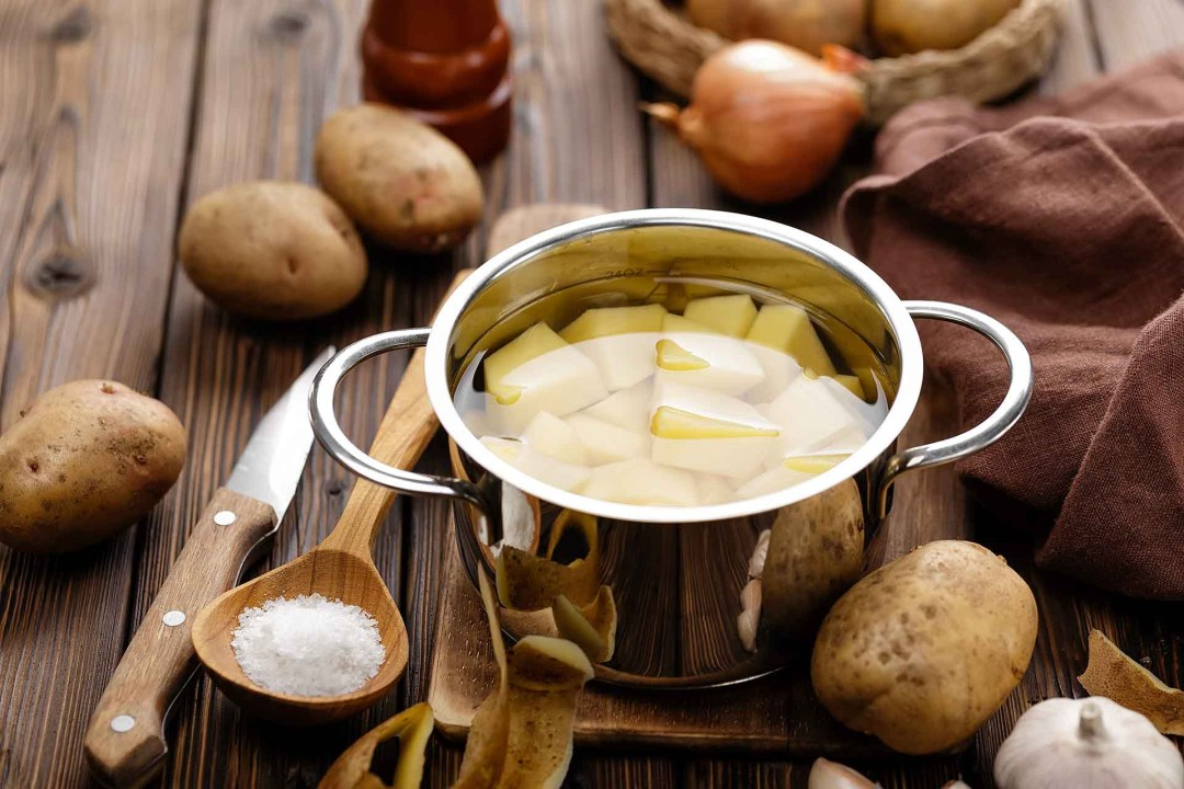 A pot full of water and cut potatoes sitting on a wooden table surrounded by whole potatoes, onions, garlic, and a knife.