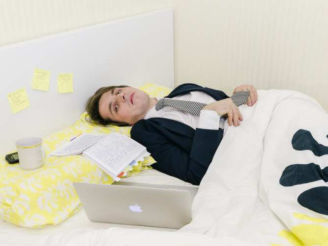 man-in-bad-wearing-suit-and-tie-working-from-home-in-bed-joke_t20_rKvgKX