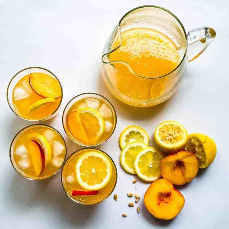 whiskey peach lemonade in cups and a glass pitcher