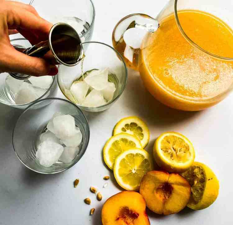 Pouring whiskey into cups with peach lemonade in a pitcher