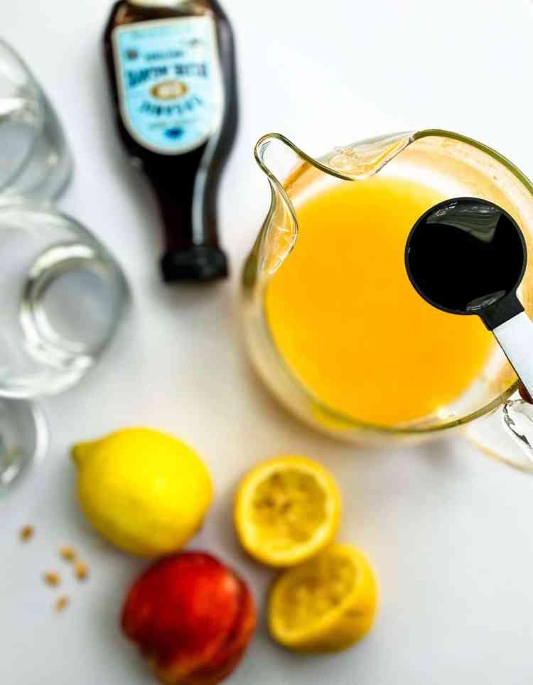 Peach lemonade with hand adding agave