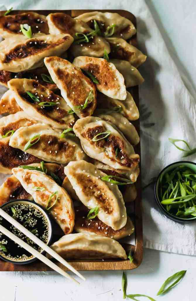 Chinese chicken dumplings with sesame soy sauce, chopsticks, and a bowl of scallions.