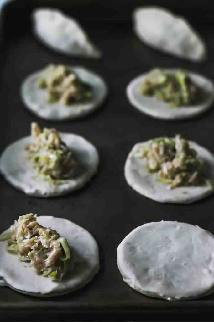 Raw dumpling dough rounds with chicken filling on top.