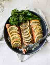 baked teriyaki salmon on a bed of rice in a black bowl with a fork.