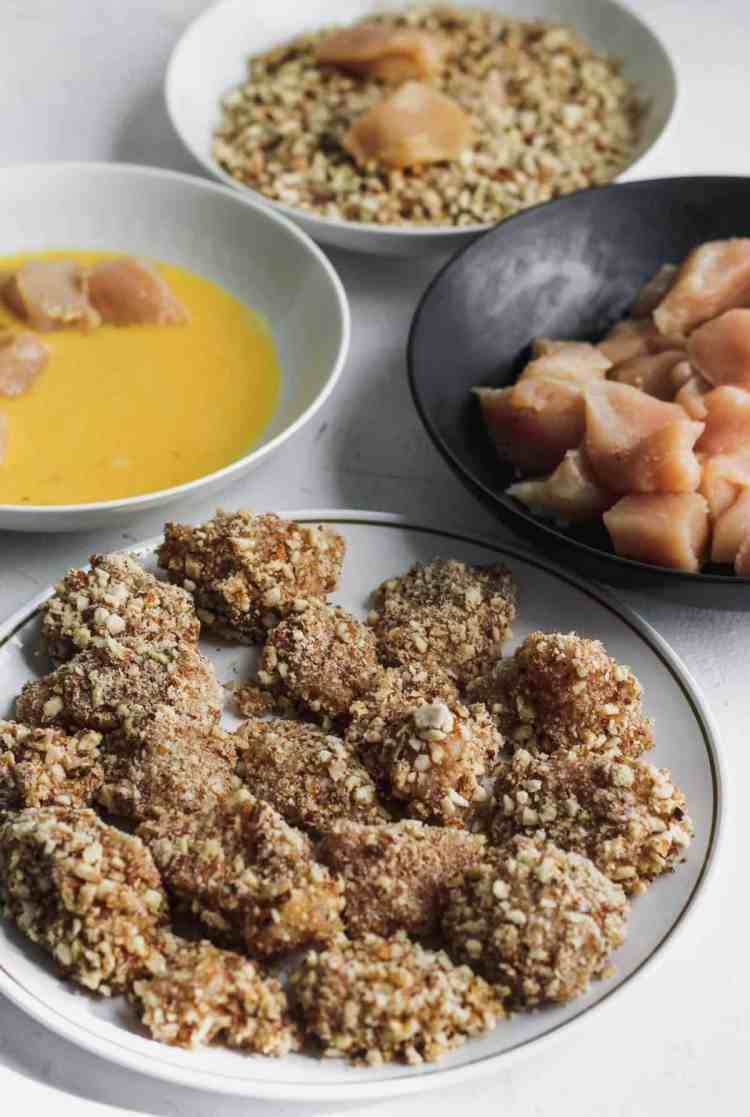 Separate bowls with the beaten egg, crushed almonds, raw chicken, and almond coated chicken.