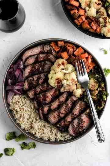Glazed balsamic steak and veggie bowls with red wine and brussels sprout leaves scattered around it.