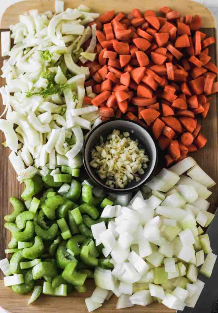 Chopped onions, sliced fennel, diced carrots and celery, and minced garlic on a wooden cutting board.