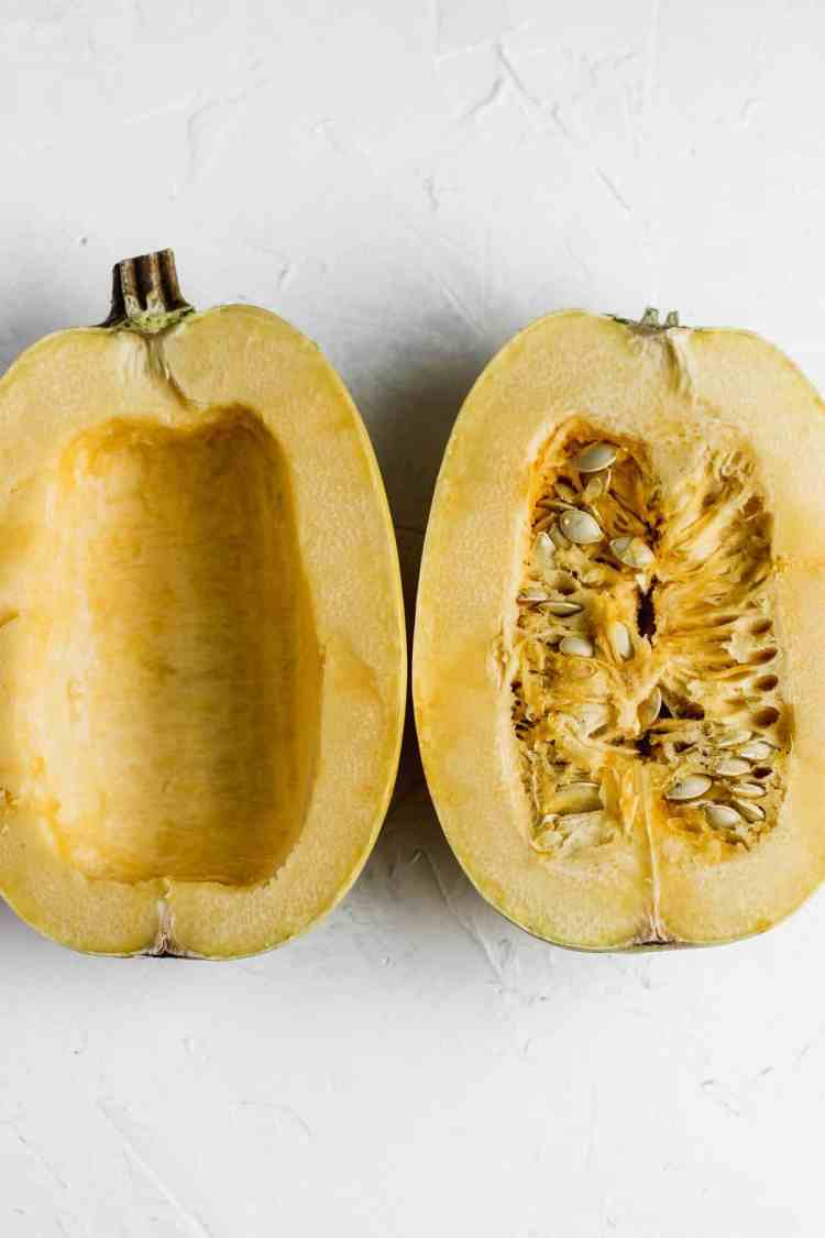 Halved uncooked spaghetti squash with seeds and inners still intact.